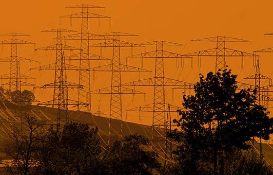 Hochspannungsmasten im Abendrot: Energietrassen zur Stromversorgung.